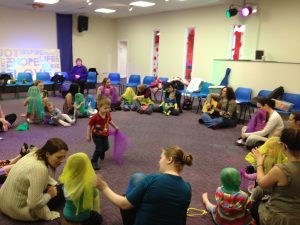 Large group of mothers and toddlers playing music