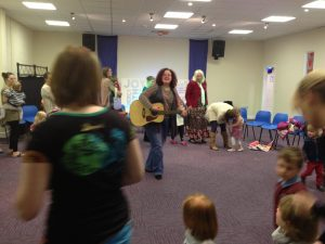 Leading a group of parents and children in a circle dance