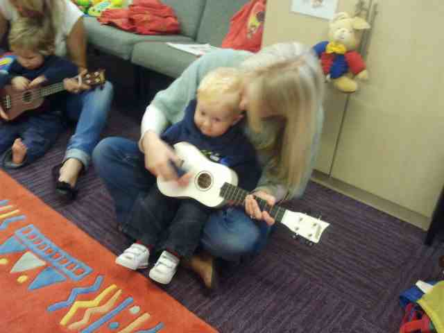 Toddler and mother playing ukulele
